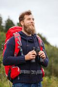 Smiling man with backpack and binocular outdoors Stock Photos