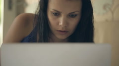 Girl in a hotel room talking on the Internet through your macbook. - stock footage