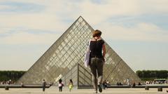 Tourist walks towards the Louvre in Paris - stock photo