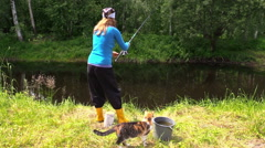 Woman fish in pond, cat fawn along feet. Fun free time nature Stock Footage