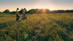 Two kids with dog walking in the field in the evening, love, together Stock Footage