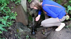 Girl Drinking Water from the Spring - stock footage