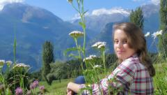 Beautiful blond girl sitting in a field of flowers over an alpine landscape Stock Footage