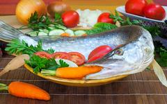 fish and components for her preparation: vegetables, spices, parsley. - stock photo