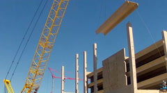 Stock Video Footage of Tall Crane Lowering Large Concrete Block At Contruction Site