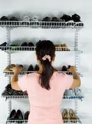 Woman selecting footwear from the shoe rack mounted on wall Stock Photos