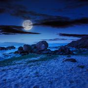 sea wave breaks about boulders at night - stock photo