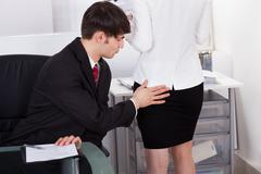 Pervert businessman touching female colleague's buttock in office Stock Photos