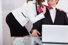 young businesswoman pulling male colleague's tie while seducing him at desk i - stock photo