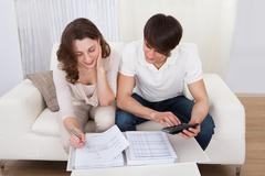portrait of young happy couple calculating budget - stock photo