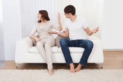 Couple who have fallen out over a disagreement sitting on a sofa Stock Photos