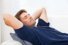 closeup of mid adult man sleeping at home - stock photo