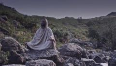 Man meditates on rocks timelapse front view Stock Footage