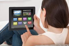 Rear view of young woman using various applications on digital tablet at home Stock Photos
