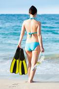 Full length rear view of woman in bikini holding diving equipment at seashore Stock Photos