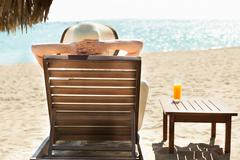 rear view of woman relaxing on deck chair at beach resort - stock photo