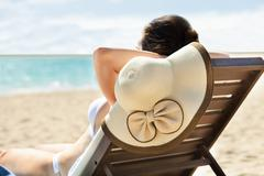 Woman with sunhat relaxing on deck chair Stock Photos