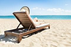Woman sunbathing on deck chair at beach Stock Photos