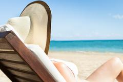 woman sunbathing on deck chair at beach - stock photo