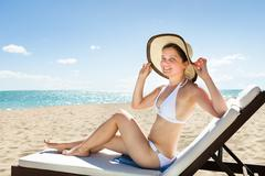 Woman in bikini relaxing on deck chair Stock Photos
