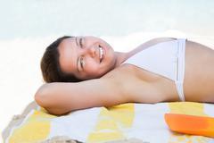 woman in bikini top lying on beach towel - stock photo