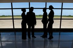 Photo of silhouetted businesspeople standing against airport window Piirros