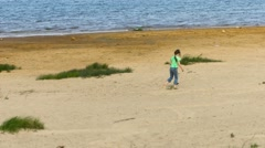 Little girl walking on a sandy shore of the lake Stock Footage