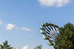 Spinning enterprise behind trees in an amusement park Stock Photos