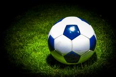 soccerball in the spotlight on a soccer field - stock photo