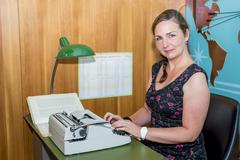 woman in working in a sixties style travel agency - stock photo