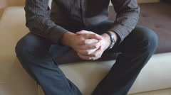 Business man on sofa, waiting anxious snapping his fingers, holding hands, fist Stock Footage