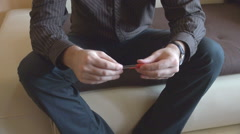 Anxious irritated man home lying on couch, play with red color pen, body view Stock Footage