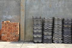 Stack roofing tiles and red brick for building construction Stock Photos