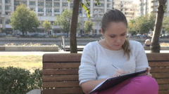 Student girl in park exam learning, study take notes with pen and papers, stress - stock footage