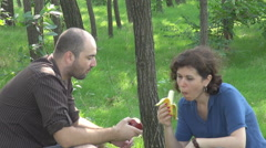Picnic in green wild forest couple outdoors eating fresh fruits red apple banana Stock Footage