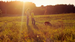 Sister and brother spending time with dog in the field, sunset, love, family Stock Footage