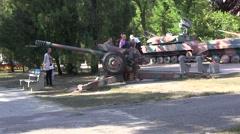 Children play near a military gun Stock Footage
