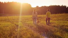 Sister and brother spending time with happy dog in the field, sunset, love Stock Footage