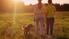 Girl and boy with happy dog in the field in the evening, happiness, freedom Stock Footage