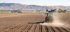 Farmer plows rows fall planting tractor farm implements Stock Photos