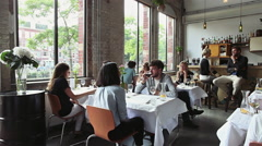 Many Young People Sitting and Talking in Stylish Restaurant Stock Footage