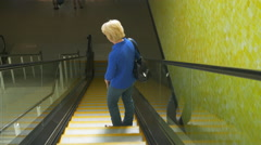 woman riding down an escalator 4k - stock footage