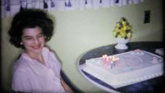 1177 - birthday girl with big hair next to her cake - vintage film home movie Stock Footage