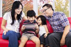 Family sharing digital tablet for play Stock Photos