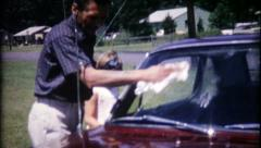 1173 - dad is cleaning the windows on the new car - vintage film home movie Stock Footage