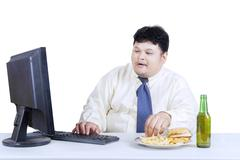 Stock Photo of obesity businessman working while eating