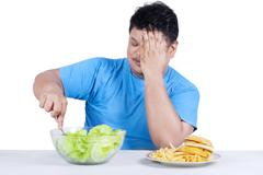 Overweight person chooses to eat salad Stock Photos