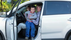 Young son sitting on father`s knees and looking new buying car inside Stock Footage