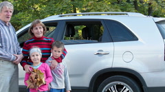 Four people happy family standing near car and looking at camera - stock footage