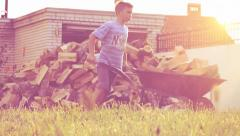 Young teenager pushing the wheelbarrow with wood pieces Stock Footage